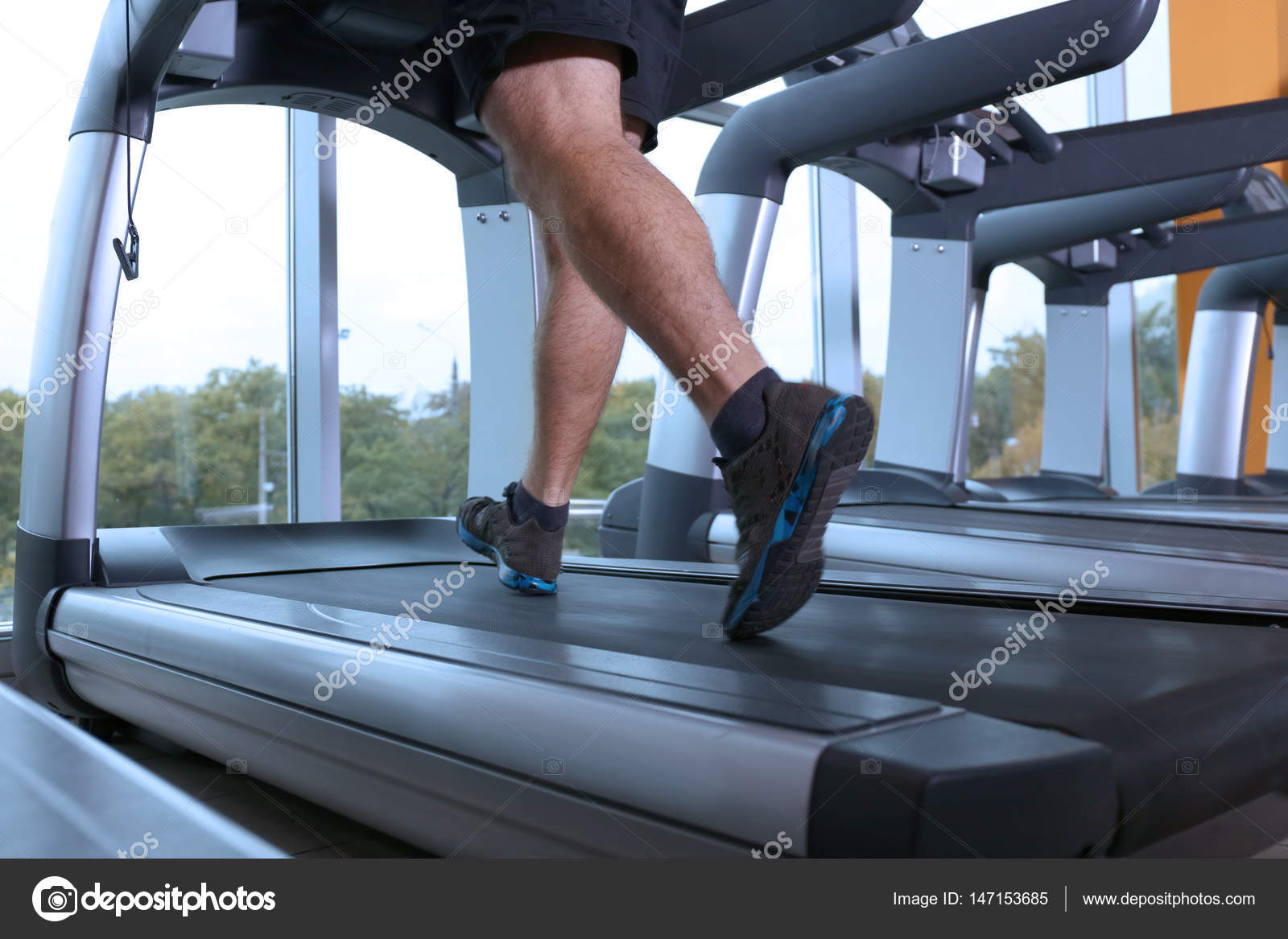 African American Man Running On Treadmill In Gym Stock Photo