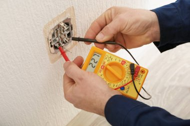 Electrician measuring voltage of socket