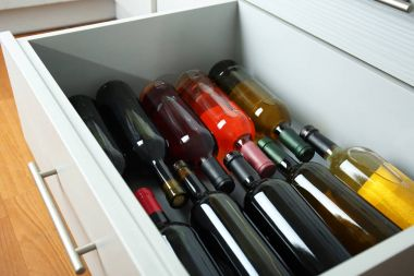Kitchen drawer with assortment of wine bottles