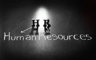 Letters HR and text HUMAN RESOURCES written with chalk on blackboard background