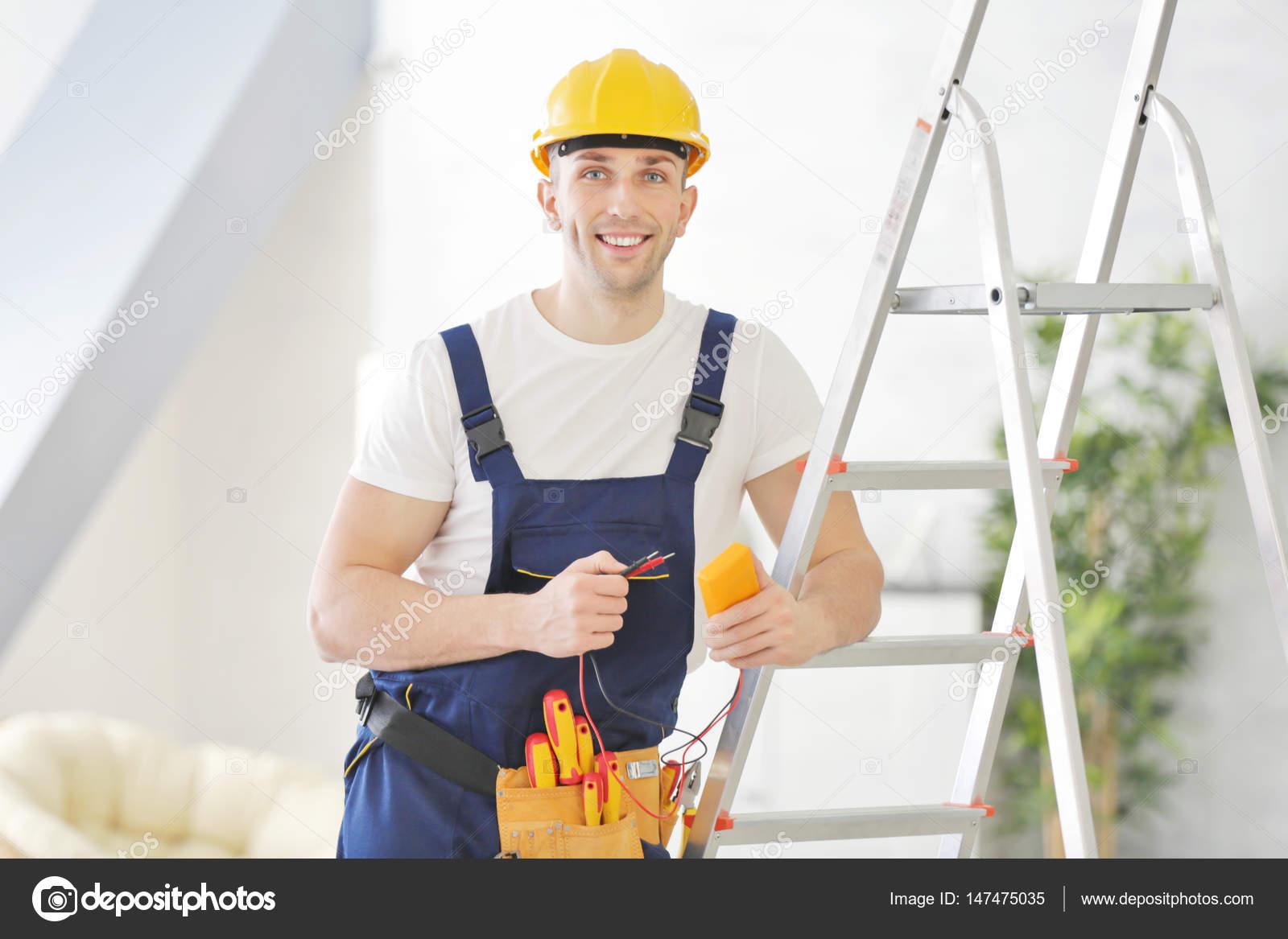 Elettricista in piedi vicino a sgabello u foto stock belchonock