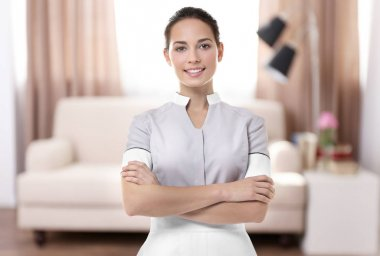 Chambermaid standing with crossed hands