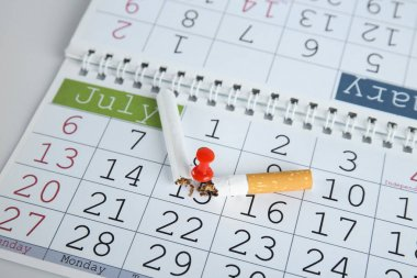 Broken cigarette pinned to calendar, closeup