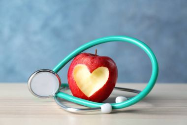 Apple with heart-shaped cut and stethoscope