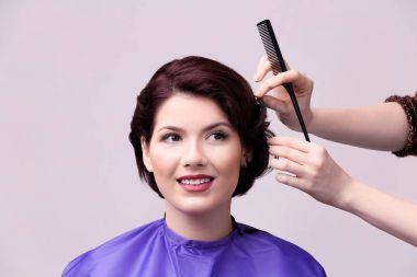 Hairdresser making beautiful haircut