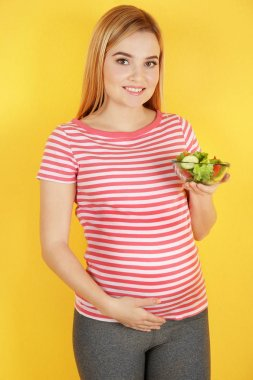 pregnant woman holding bowl with salad