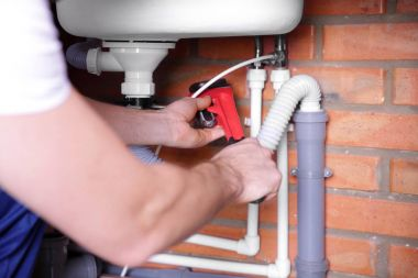 Plumber repairing sink pipes