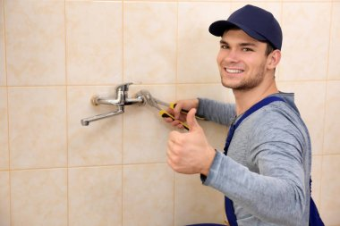 handsome plumber fixing faucet
