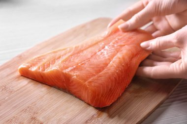 Hands putting salmon on cutting board