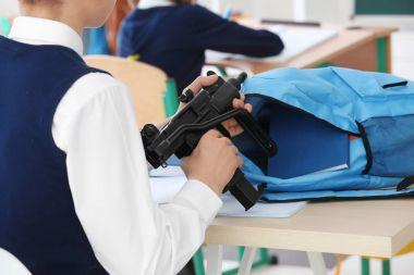 schoolboy holding machine gun