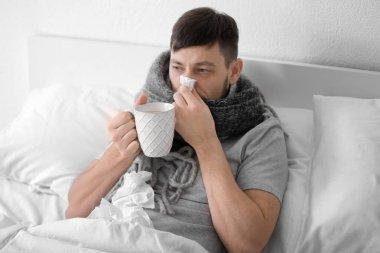 ill man drinking hot tea