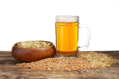 Glass of beer and barley seeds on wooden table and white background