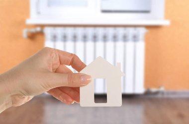 Female hand holding house figure
