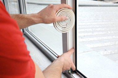 Hands of worker applying strip onto window