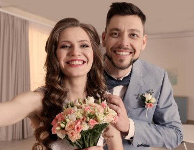 Happy wedding couple making selfie at home
