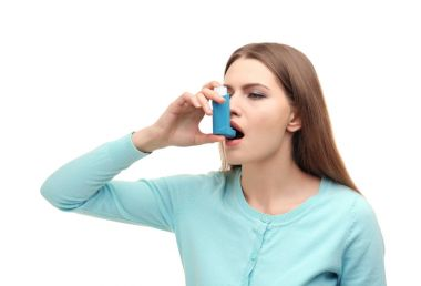 Young woman using asthma inhaler