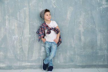 Cute stylish boy near grunge wall