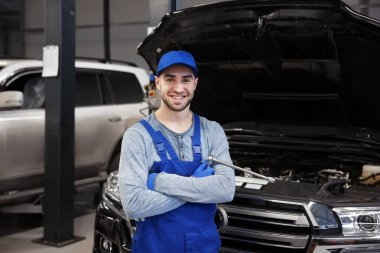 Young mechanic with crossed arms