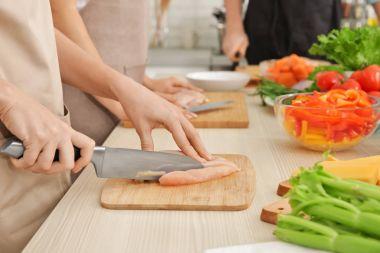 Woman cutting chicken fillet