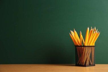Pencils in metal holder on chalkboard background