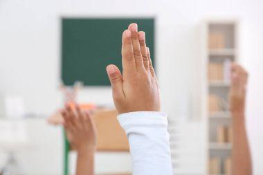 Children raising hands up in classroom