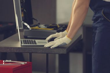 Auto mechanic working with laptop