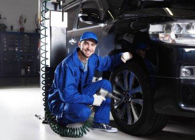 Young mechanic changing wheel