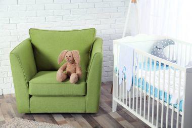 Cute bunny toy on green armchair