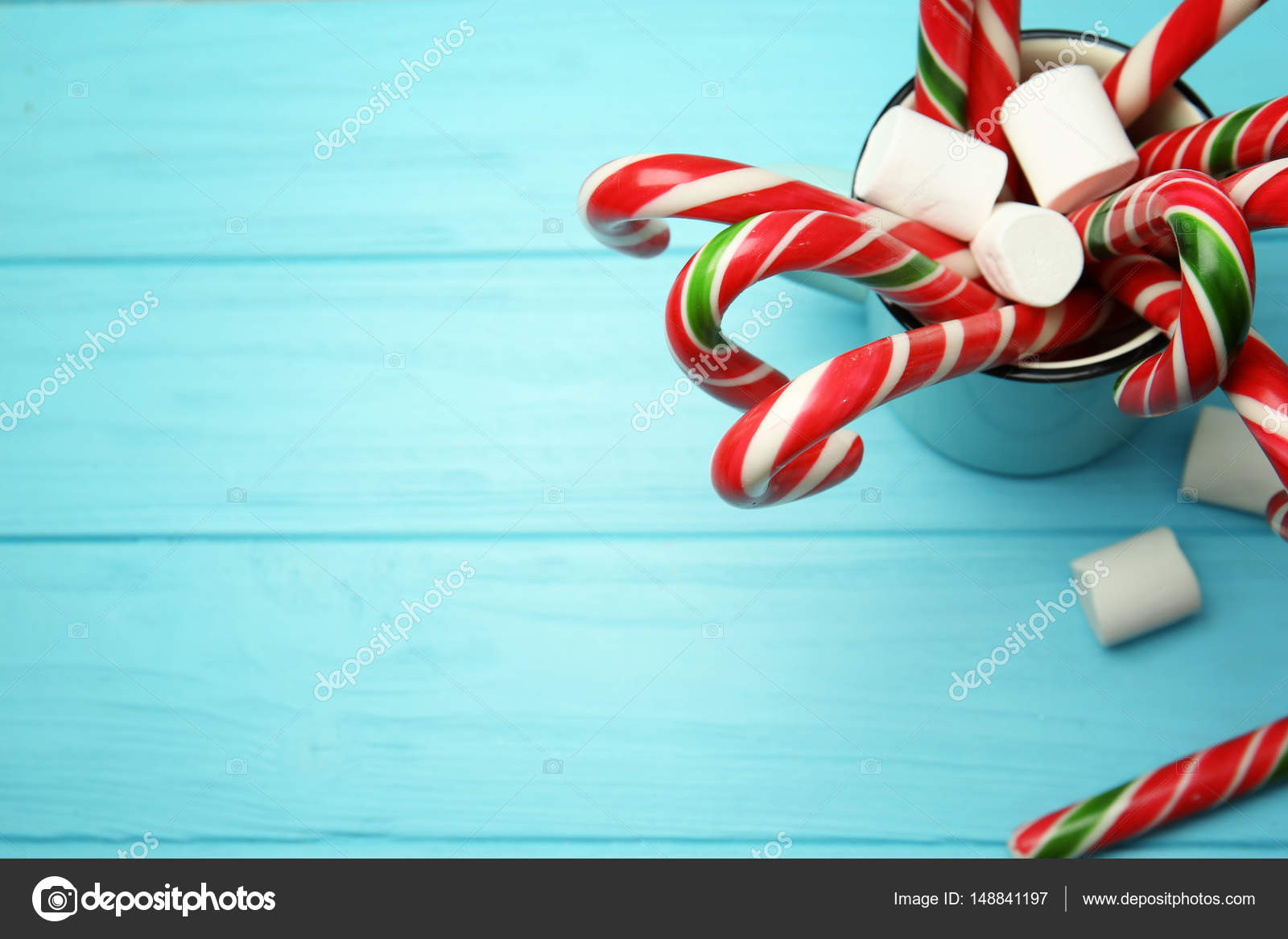 christmas candy canes and marshmallows in cup on color wooden background photo by belchonock