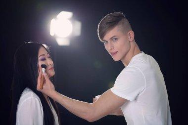 Male artist doing makeup
