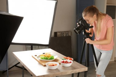 Young woman photographing food in photo studio stock vector