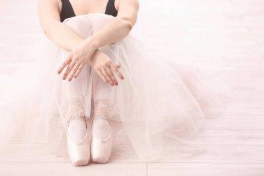Young ballerina sitting on floor