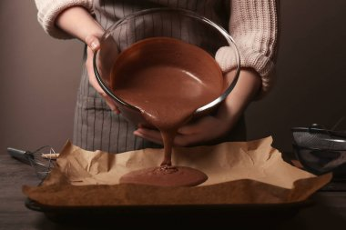 Woman pouring cocoa liquid dough