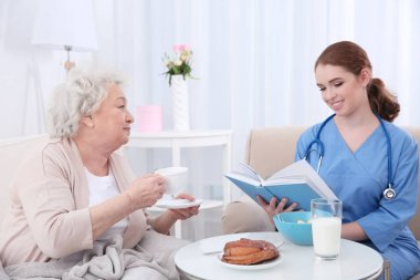 Nurse caring about elderly woman in light room