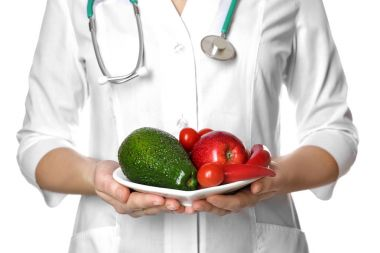 Doctor holding plate with healthy foods