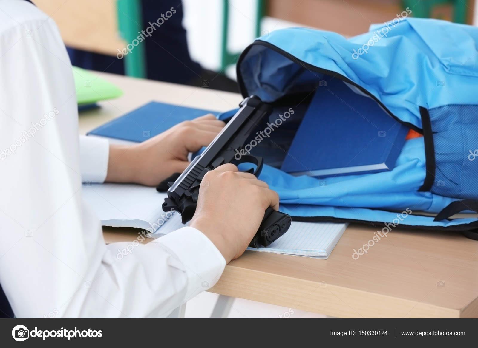 écolier assis au bureau avec pistolet u photographie belchonock