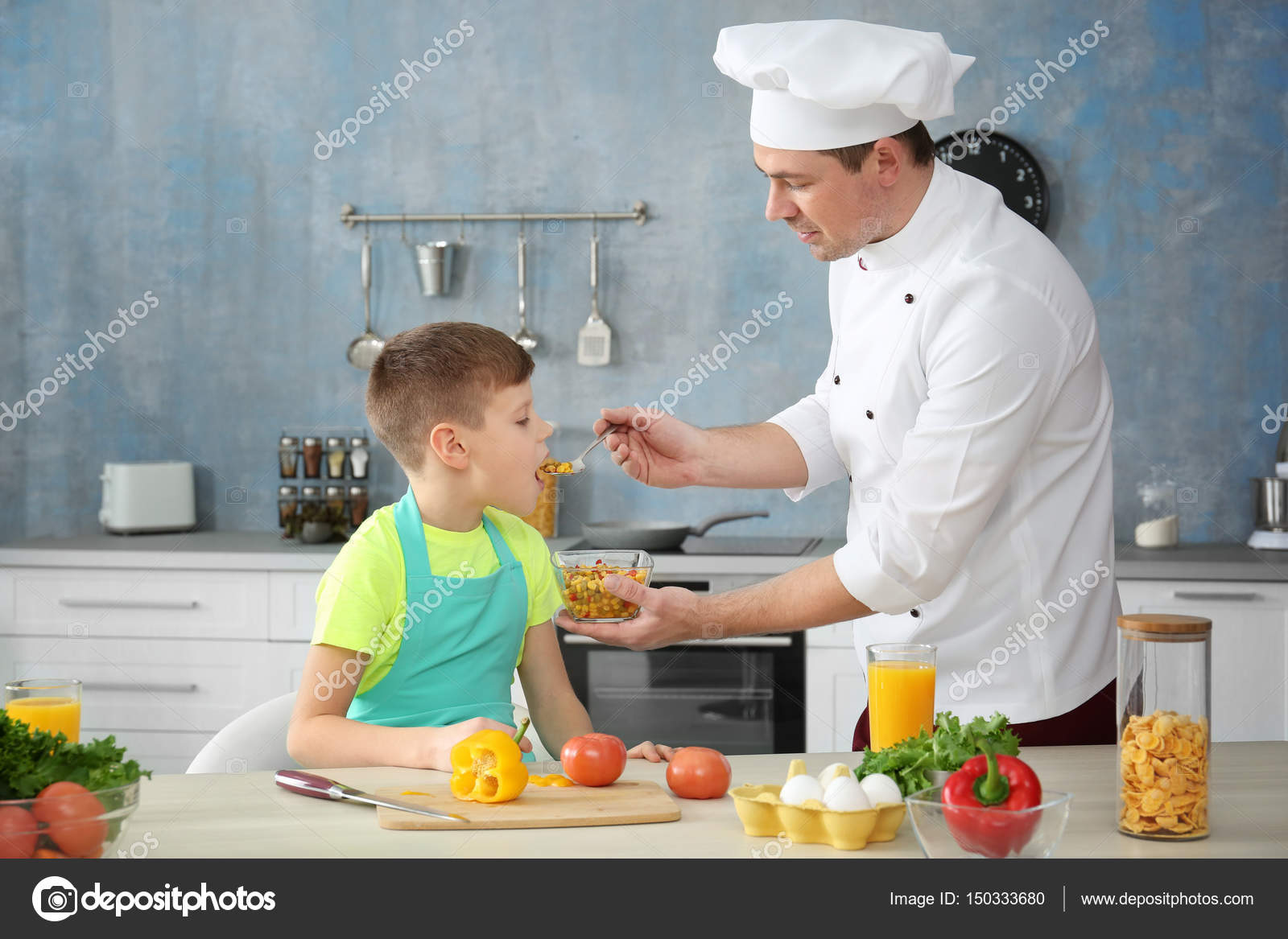 Father feeding son in kitchen while cooking together — Stock Photo ...