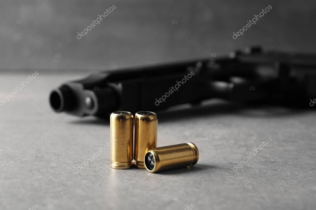 Bullets and gun on gray table stock vector