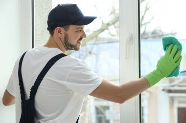 Young man cleaning window