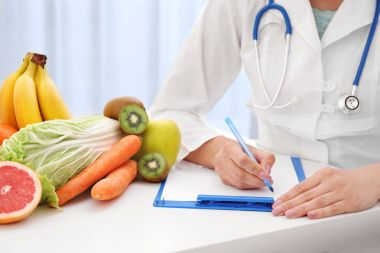 Nutritionist doctor writing diet plan