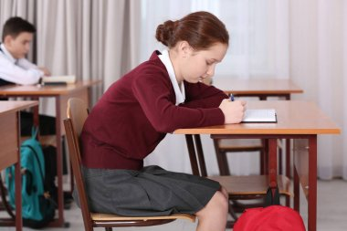 Incorrect posture concept. Pupils sitting at desk in classroom