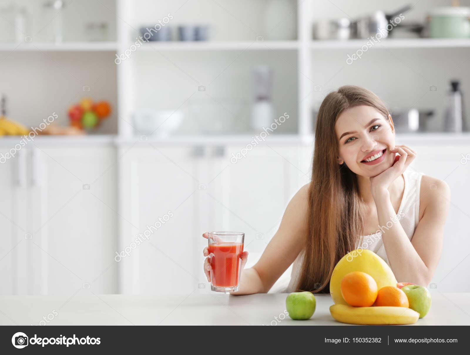 Woman tasting juice at kitchen — Stock Photo © belchonock #150352382