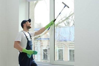 man washing window in office