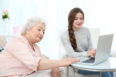 Beautiful girl with grandmother using laptop at home
