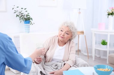 Nurse giving glass of water to elderly woman