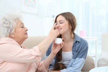 Beautiful girl and grandmother taking skin care on couch at home