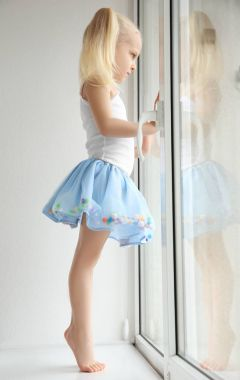 girl standing on windowsill