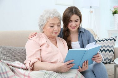 Beautiful girl with grandmother reading book on couch at home