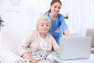 Nurse helping elderly woman to work on laptop in light room