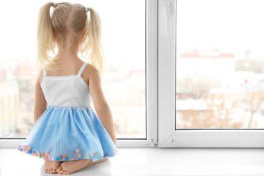 girl sitting on windowsill